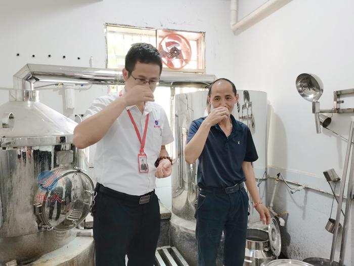 6.18蒋老师正在品尝刚刚蒸出来的美酒