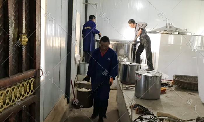 6.2工人正在忙着用蒸酒设备蒸大米